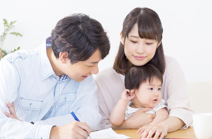 リフォームのプラン設計をする夫婦と赤ん坊